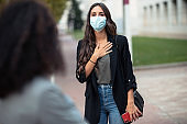 Beautiful young business woman wearing surgical mask and greeting to her friend in the street at Covid19 outbreak. Social distancing and new normal concept.