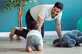 Smiling young father has fun with little baby while are crawling on the floor together at home.