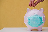 Adult hand putting money into a Piggy bank wearing Face Mask, Financial crisis and market crash
