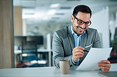 Happy businessman in office looking at document, portrait.