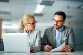 Business concept. Two business people sitting at desk with document and laptop, focus on laptop.