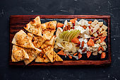 Top view of a serving board with variety of cheese, almonds, apple, pizza bread. Healthy eating.