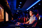 Professional young gamer with headphones playing competitive video game at internet cafe or playroom, portrait.