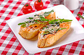 Italian Appetizer Bruschetta with Salmon, parmesan, balsamic vinegar and fresh arugula on white plate in italian restaurant background, top view. Italy food. Close up.