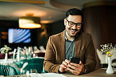 Cheerful man using smart phone in the restaurant, close-up, portrait.