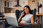 Close-up portrait of a woman using laptop and smart phone while sitting in armchair at home.