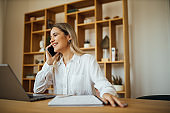 Smiling entrepreneur working at home office, talking on smart phone, portrait.