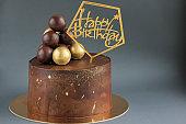 Chocolate birthday cake with gold decorations. Holiday, celebration, stylish, minimal concept.