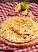 Rustic pizza with cheese, apple and cinnamon served on a wooden board for a dinner in italian restaurant background, top view. Fruit dessert pizza