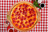 Neapolitan Pepperoni pizza with sausage, salami, cheese, vegetable and tomatoes sauce, served on a wooden board for a dinner in italian restaurant background, top view. Italy food. Pizza from wooden oven.