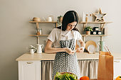 Young caucasian woman is tying an apron, preparation to cooking food.