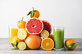 Creative composition of slices citrus fruit and glasses of juice. Seasonal fruits are source of vitamin C and strengthen immunity