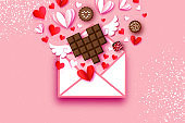 Love Chocolate. Valentines Day Greeting Card. Red white hearts paper cut style and dessert, chocolate, candy on coral. Origami Happy holidays. 14 February. Valentines postcard with wings.