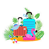 Suitcases on the beach. Travel bag with hat on the sunny beach. Giant inflatable Pink Flamingo.Flipflop, ball and palm leaves. Summer holidays. Sunny days. Holidays. Time to travel. Weekend. Flat.