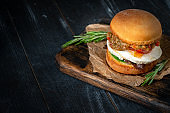 Homemade Italian vegetarian Burger with mozzarella and fried eggplant on a wooden Board on a dark background, rustic style