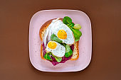 Healthy breakfast sandwiches concept. Bread toasts with fried eggs and green salad on pink plate on brown background, top view. Dietary food