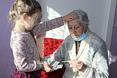 Midsection of care aid giving medicines to resident in nursing home