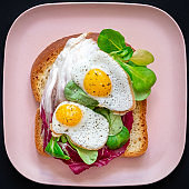 Healthy breakfast sandwiches concept. Bread toasts with fried eggs and green salad on pink plate on black background, top view. Dietary food