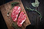 Raw chuck roll steaks premium beef with seasonings on wooden board, top view, rustic stule