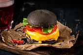 Cheeseburger with a black bun on a kraft paper on wooden Board, homemade Japanese Burger