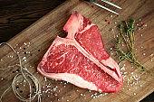 raw t bone steak on wooden Board rustic style