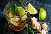 Whiskey and Cola cocktail with lime, mint, brown sugar and ice, alcoholic drink in a glass on a dark wooden background, copy space