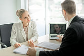 Boss businessman talking seriously about report with woman employee at desk in office