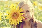 Portrait of cute girl enjoying of freedom in the sunflowers field