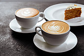 two cups of coffee on black stone background