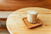 A beautiful cup of cappuccino with latte art in the wooden space background.