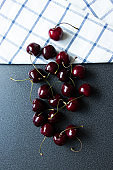 Sweet cheries, summer, fruit. Beautiful sweet dark cherries and kitchen towel with a line. Top view.