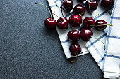 Summer background. Sweet dark cherries and kitchen towel with a line. Top view.