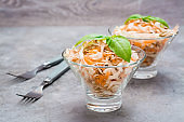 American ready-to-eat cole slaw salad of cabbage, celery, carrots and apples with basil leaves in glass bowls on the table. The concept of healthy and proper nutrition.