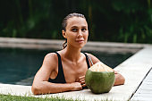 portrait of cute girl with coconut cocktail in the tropical pool.