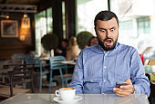 Shocked handsome young man using smartphone