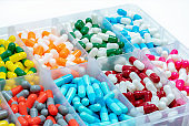 Colorful capsules pill in plastic box.  Pharmaceutical industry. Pharmacy drugstore products. Drug interactions. Healthcare and medicine background. Bright color of capsules pills in plastic tray.