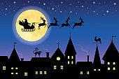 Silhouette of a santa on a sledge harnessed by magic reindeer flying over a town.
