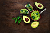 """Avocado  on dark  wooden Background.  Guacamole sauce with avocado toast, mint and herbs. Top view. Copy space""""n"""