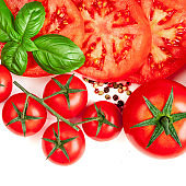 Creative layout made of Tomato, herbs and spices. Red tomatoes and basil leaves isolated on white background. Flat lay. Top view