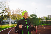Active elderly Caucasian elderly women of 90 years practice Nordic walking with ski poles on a track with a red rubber coating. Active holidays. A fit woman. Healthy lifestyle for the elderly