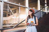 Woman using smart phone while standing on railway station platform. Travel and vacation concept. Theme Transportation And trip. tourist woman in hat checking electronic ticket for train or plane