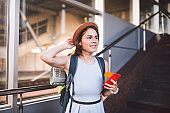 Enjoy travel. Female waiting train on station with backpack, using smart phone. Tourist makes plan, watching schedule route railway, railroad transport concept. woman wait train on railway station