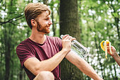 People eat banana and drink water from plastic bottle while sitting on log in wood. Couple hikers take break for food and drink in forest on fallen tree trunk. Stop for picnic, trail forest walk