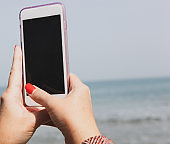 A young girl takes selfies on the beach