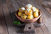 Young, boiled potatoes with sour cream and dill on a wooden table