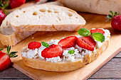 Strawberry sandwiches with cottage cheese and mint on a cutting board