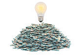 Light bulb on the heap of dollar packs, 3D rendering isolated on white background