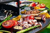 Stewed vegetables and grilled meats, tomatoes, zucchini, peppers, beef, pork, seafood. Delicious lunch for the holiday
