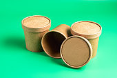 Empty paper disposable cups fo takeaway food container isolated on green.