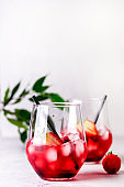 Glasses of Tasty Cranberry Cocktail with Ice Cubes on light Gray Background Alcoholic Drink Straws Vertical